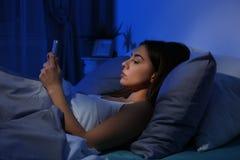 Jeune femme avec le téléphone portable la nuit photographie stock libre de droits