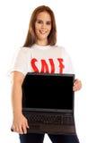 Jeune femme avec le T-shirt et l'ordinateur portable de ` de vente de ` Image libre de droits