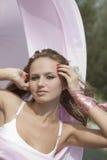 Jeune femme avec le tissu rose oscillant dans la victoire Photos libres de droits