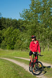 Jeune femme avec le vélo de montagne dans la nature Images libres de droits