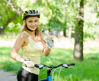Jeune femme avec le vélo de montagne et la bouteille de l'eau à disposition Images libres de droits