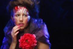 Jeune femme avec le visage artistique tenant la grande fleur rouge Images stock