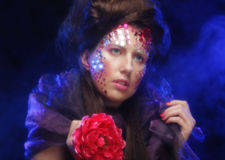 Jeune femme avec le visage artistique tenant la grande fleur rouge Image stock