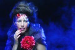 Jeune femme avec le visage artistique tenant la grande fleur rouge Image libre de droits