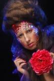 Jeune femme avec le visage artistique tenant la grande fleur rouge Photographie stock