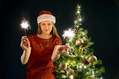 Jeune femme avec les bougies de scintillement, l'arbre de Noël et le fond décoratif de bokeh d'éclairage Elf et sapin avec des dé image libre de droits