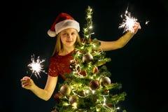 Jeune femme avec les bougies de scintillement, l'arbre de Noël et le fond décoratif de bokeh d'éclairage Elf et sapin avec des dé photo libre de droits