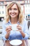 Jeune femme avec les cheveux blonds buvant d'un café Photographie stock libre de droits