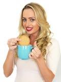 Jeune femme avec les cheveux blonds détendant et trempant un biscuit dans une tasse de thé Photos libres de droits