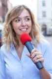 Jeune femme avec les cheveux blonds et le microphone Photos libres de droits