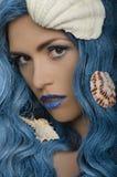 Jeune femme avec les cheveux et les coquillages bleus image stock