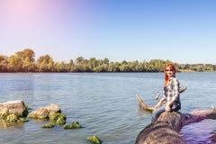 Jeune femme avec les cheveux rouges à la rivière Images stock