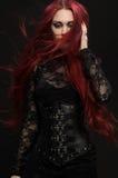 Jeune femme avec les cheveux rouges dans le costume gothique noir images libres de droits