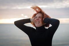 Jeune femme avec les cheveux rouges saisissant à sa tête se tordant en douleur sur le fond de la mer et du coucher du soleil photographie stock