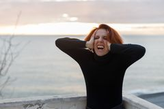 Jeune femme avec les cheveux rouges saisissant sa tête de désespoir sur le fond de la mer et du coucher du soleil photo libre de droits