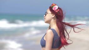 Jeune femme avec les cheveux rouges volant dans le vent et une guirlande florale dans ses cheveux dans la perspective de la mer banque de vidéos