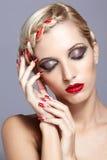 Jeune femme avec les clous rouges Images stock
