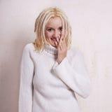 Jeune femme avec les dreadlocks blonds riant nerveusement Image stock