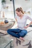 Jeune femme avec les jambes croisées se reposant avec des mains sur des hanches Photographie stock