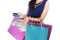 Jeune femme avec les paniers, l'argent, et la carte de crédit Photographie stock