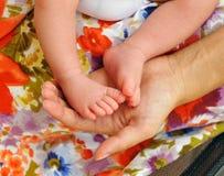 Jeune femme avec les petits pieds de son bébé dans les mains Image libre de droits