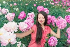 Jeune femme avec les pivoines roses Photographie stock