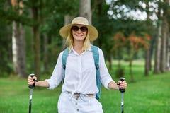 Jeune femme avec les pols nordiques de promenade photographie stock libre de droits