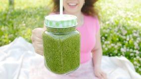 Jeune femme avec les smoothies végétaux verts en parc banque de vidéos