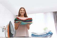 Jeune femme avec les vêtements pliés près de la planche à repasser à la maison photo libre de droits