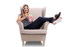 Jeune femme avec les verres 3D et le maïs éclaté se reposant dans un fauteuil Photo stock