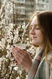 Jeune femme avec les yeux fermés et une tasse de thé appréciant le ressort Images libres de droits