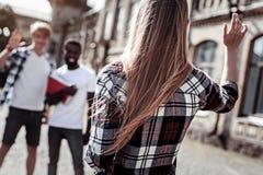 Jeune femme avec plaisir saluant ses amis Photographie stock libre de droits