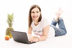 Jeune femme avec rire d'ordinateur et de fruits image libre de droits