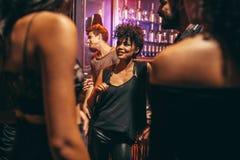 Jeune femme avec ses amis à la boîte de nuit Image libre de droits