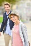 Jeune femme avec son ami marchant dans les rues de ville Photos stock