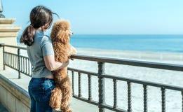Jeune femme avec son crabot sur la plage Photo libre de droits