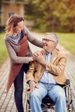 Jeune femme avec son père handicapé sur le fauteuil roulant en parc Image libre de droits
