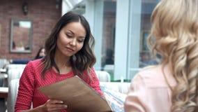 Jeune femme avec un ami passant commande au serveur tenant le menu Image libre de droits