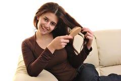 Jeune femme avec un balai de cheveu dans sa main Image stock