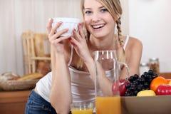 Jeune femme avec un bol de fruit Image stock