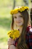 Jeune femme avec un bouquet des pissenlits et d'une guirlande sur sa tête Photos stock