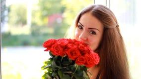 Jeune femme avec un bouquet des roses rouges près d'une fenêtre ouverte Une belle fille apprécie l'arome des fleurs banque de vidéos