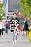 Jeune femme avec un chapeau de bouche, Pékin, Chine Photographie stock libre de droits