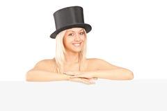 Jeune femme avec un chapeau posant derrière un panneau Photos libres de droits