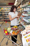 Jeune femme avec un chariot à un supermarché Image stock