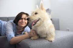 Jeune femme avec un chien à la maison Photo stock