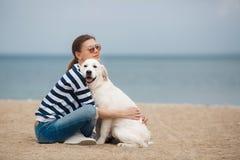 Jeune femme avec un chien sur une plage abandonnée Photographie stock libre de droits