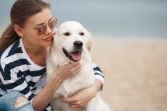 Jeune femme avec un chien sur une plage abandonnée Photo stock