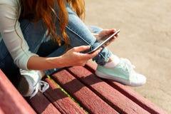 Jeune femme avec un coffe à aller marquer sur tablette le PC sur un banc Photographie stock