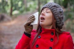 Jeune femme avec un froid ou une grippe éternuant Photo stock